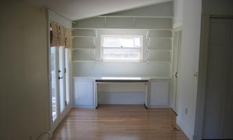Custom built office space desk with custom shelving and cabinets, and hardwood floors and lots of natural light