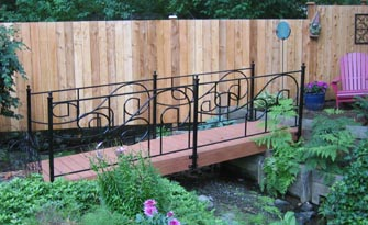 Beautiful handcrafted wooden bridge with custom wrought-iron railing.